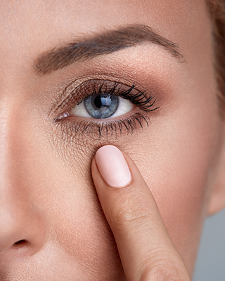 An Image of a woman pointing at her eye
